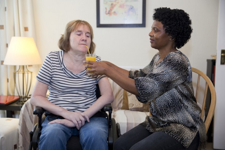 Disabled lady being helped to drink by live-in carer