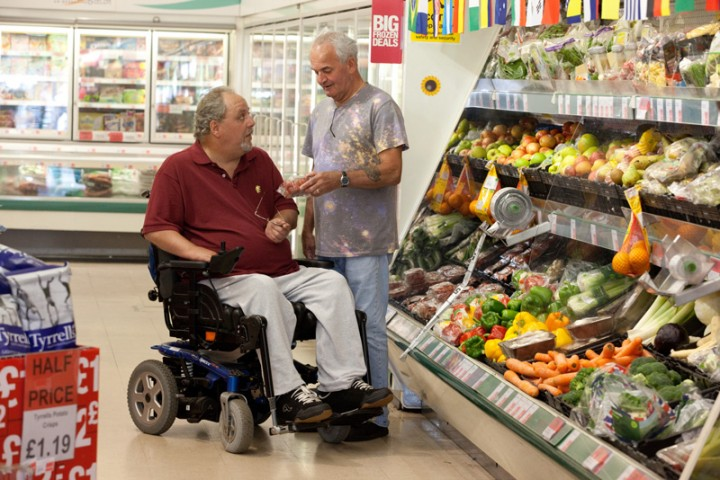 Disabled man in supermarket with his live-in carer