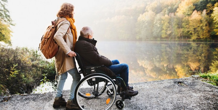 Man in wheelchair beside a lake with holiday carer